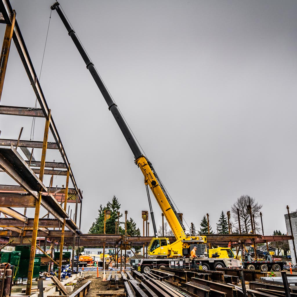 Omega Morgan Sarens Grove crane hook services helping Evergreen Erectors to erect steel for the new Mirror Lake Elementary School building in Federal Way