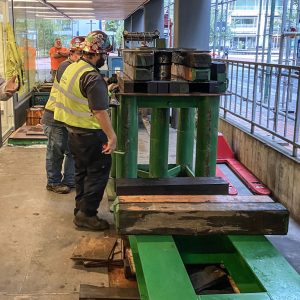 Omega Morgan Machinery Moving crew members setting up a steel base to prepare for replacing a bearing pad in a parking garage