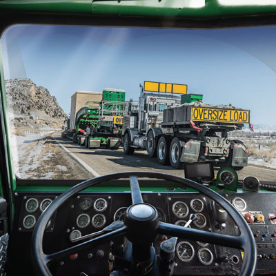 from a truck drivers point of view behind the wheel looking through the windshield at other Oversize Load trucks going up a paved road on a remote area