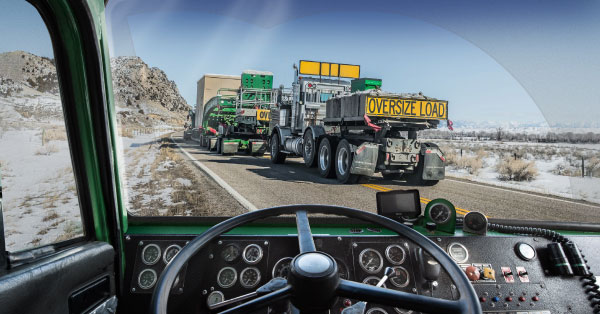 from a truck drivers point of view looking through the windshield at other Oversize Load trucks going up a paved road on a remote area