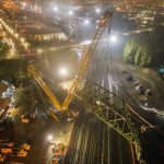 nighttime scene taken from an aerial perspective of Omega morgan crane team lifting an aging bridge in Tacoma, Washington