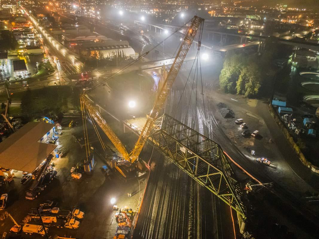 nighttime scene taken from an aerial perspective of Omega morgan crane team lifting an aging bridge in Tacoma, Washington