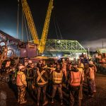 Omega Morgan crane team huddle in front of Tacoma bridge move site