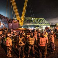 selected thumbnail of Omega Morgan crane team huddle in front of Tacoma bridge move site