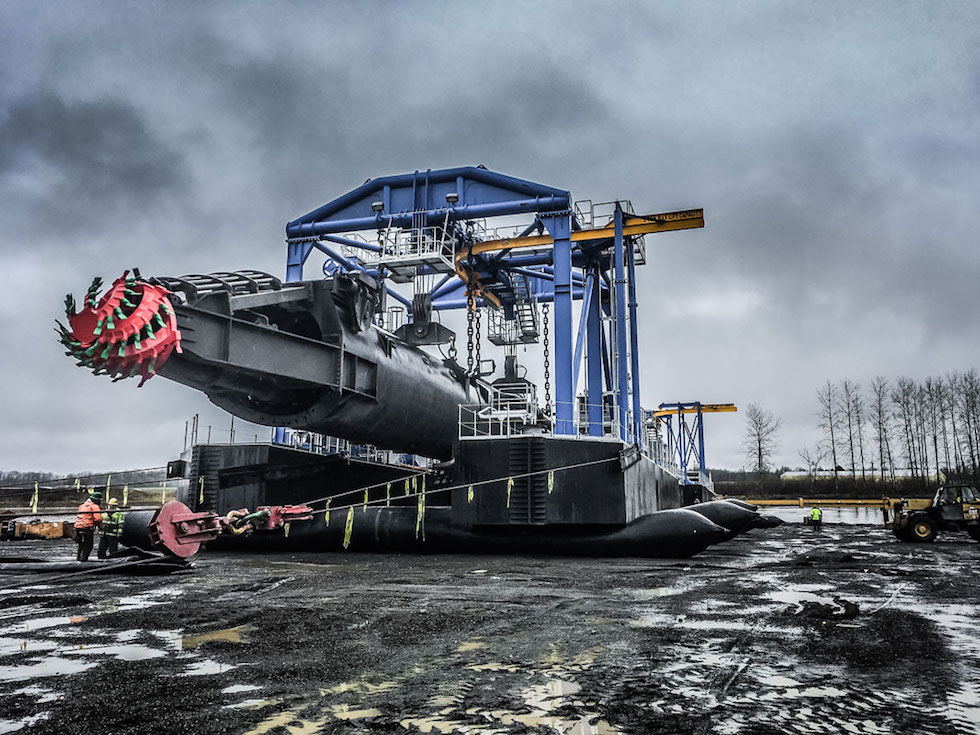 an enormous suction dredge in a rockpit being moved by Omega Morgan Millwright team in CalPortland's rockpit in Scappoose, Oregon