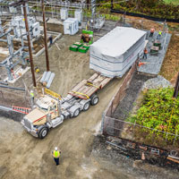 selected button thumbnail of View from the sky of Omega Morgan machinery moving teams moving a transformer at Vashon Island Substation