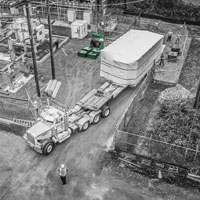 deselected button thumbnail of View from the sky of Omega Morgan machinery moving teams moving a transformer at Vashon Island Substation