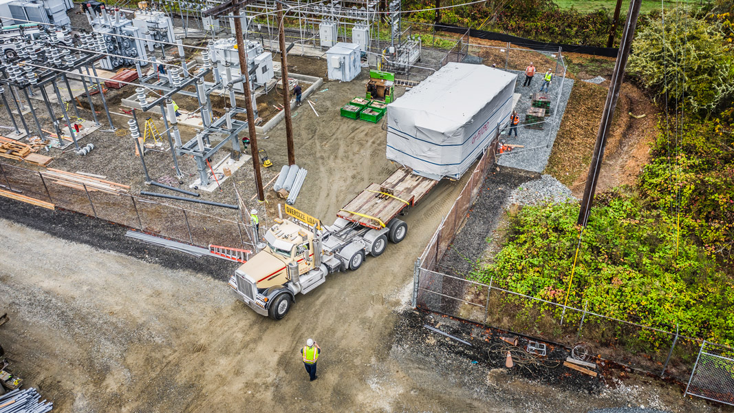 View from the sky of Omega Morgan machinery moving teams moving a transformer at Vashon Island Substation