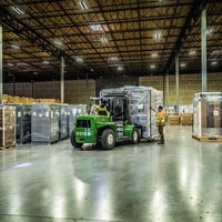 selected thumbnail button of inside the Omega Morgan Hillsboro warehouse where a forklift with a large load is being brought in