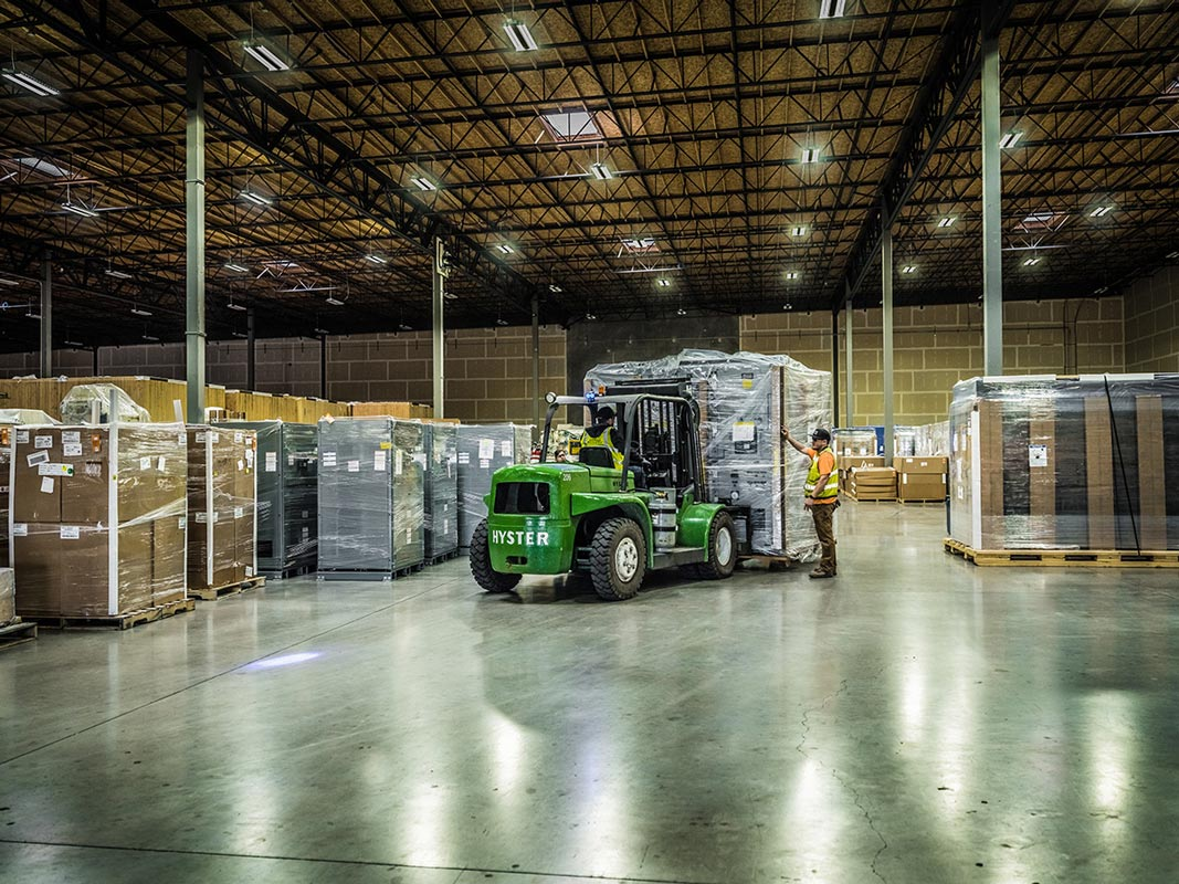 inside the Omega Morgan Hillsboro warehouse where a forklift with a large load is being brought in