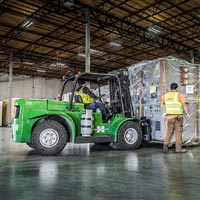 selected thumbnail button of Omega Morgan workers bring a large piece of equipment into the Hillsboro warehouse and storage facility with a forklift