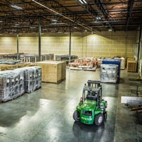 selected thumbnail button of wide angle view of the inside of an Omega Morgan warehouse and storage facility with rows of large equipment being stored alongside a warehouse forklift