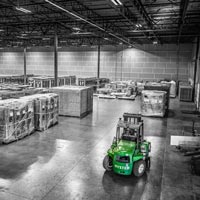 deselected thumbnail button of wide angle view of the inside of an Omega Morgan warehouse and storage facility with rows of large equipment being stored alongside a warehouse forklift