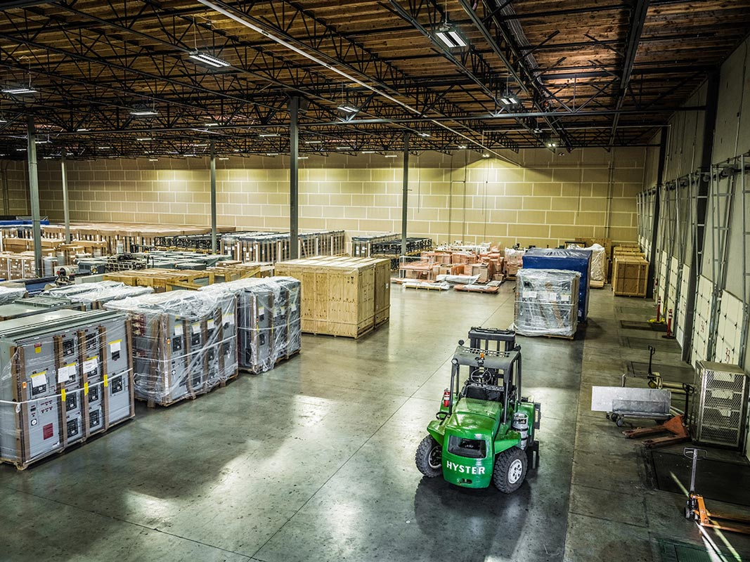 wide angle view of the inside of an Omega Morgan warehouse and storage facility with rows of large equipment being stored alongside a warehouse forklift