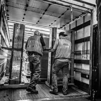 deselected thumbnail button of two warehouse workers pulling equipment out of a truck for storage