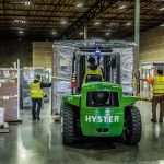 three Omega Morgan team members in the warehouse and storage facility carefully forklifting a load of equipment into place for storage