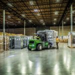 An Omega Morgan warehouse facility with a forklift bringing a large load into place for storage