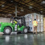 an Omega Morgan staff member carefully watches a load of data center equipment being set into place by a warehouse forklift in an Omega Morgan storage facility