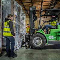 selected thumbnail button of an Omega Morgan warehouse forklift prepares to move a large piece of equipment inside an Omega Morgan warehouse and storage facility