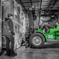deselected thumbnail button of an Omega Morgan warehouse forklift prepares to move a large piece of equipment inside an Omega Morgan warehouse and storage facility