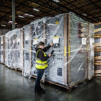 selected thumbnail button of a female Omega Morgan warehouse staff member checks large pieces of equipment being stored inside an Omega Morgan warehouse and storage facility