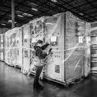 deselected thumbnail button of a female Omega Morgan warehouse staff member checks large pieces of equipment being stored inside an Omega Morgan warehouse and storage facility