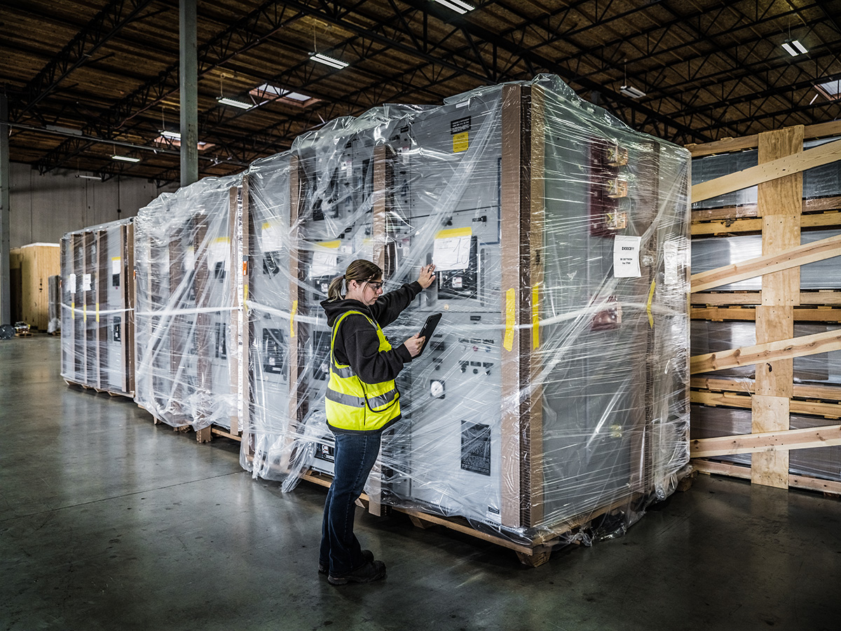 a female Omega Morgan warehouse staff member checks large pieces of equipment being stored inside an Omega Morgan warehouse and storage facility