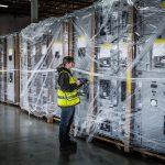 a female Omega Morgan warehouse staff member checks data center equipment being stored inside an Omega Morgan warehouse and storage facility