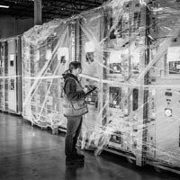 deselected thumbnail button of a female Omega Morgan warehouse staff member checks data center equipment being stored inside an Omega Morgan warehouse and storage facility
