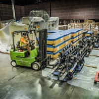 selected thumbnail button of overhead looking down at an Omega Morgan forklift preparing to move equipment inside a warehouse and storage facility
