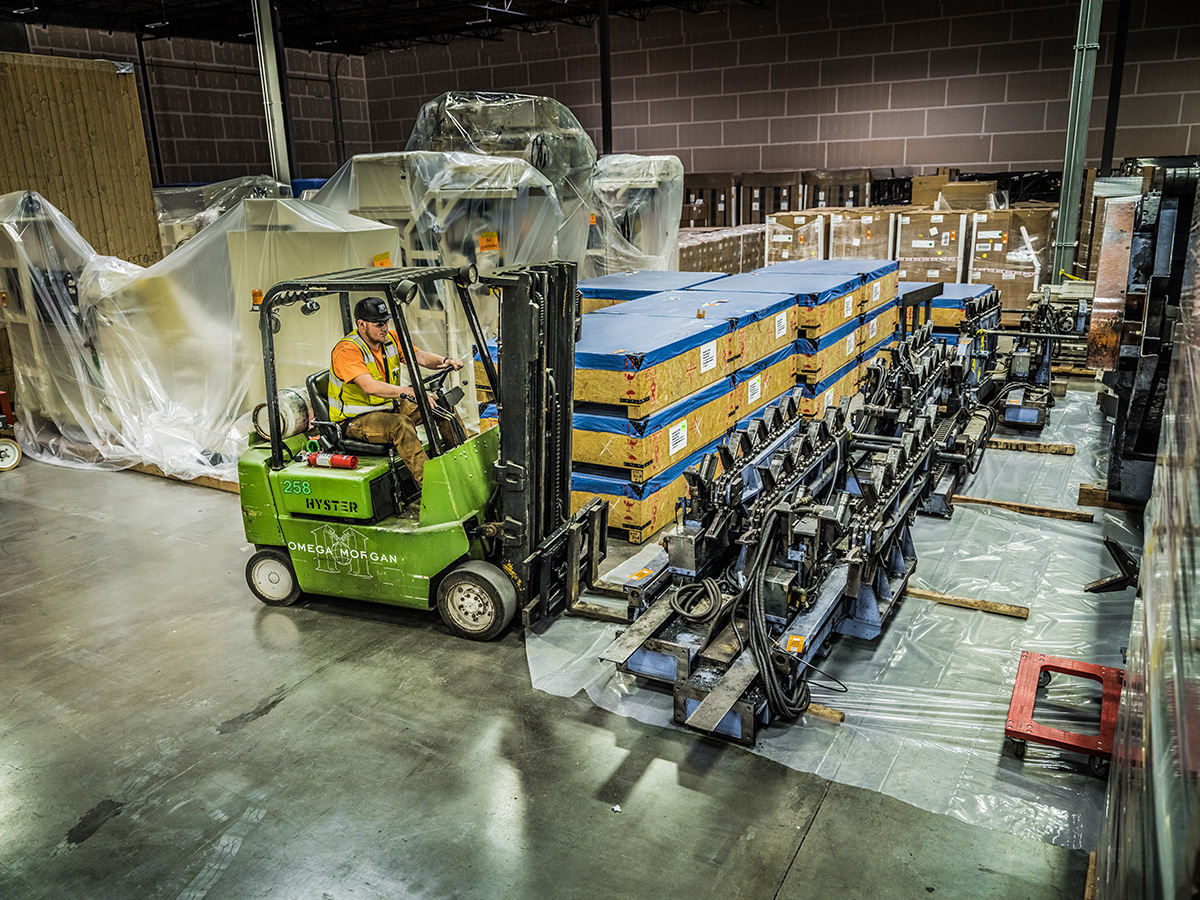 overhead looking down at an Omega Morgan forklift preparing to move equipment inside a warehouse and storage facility