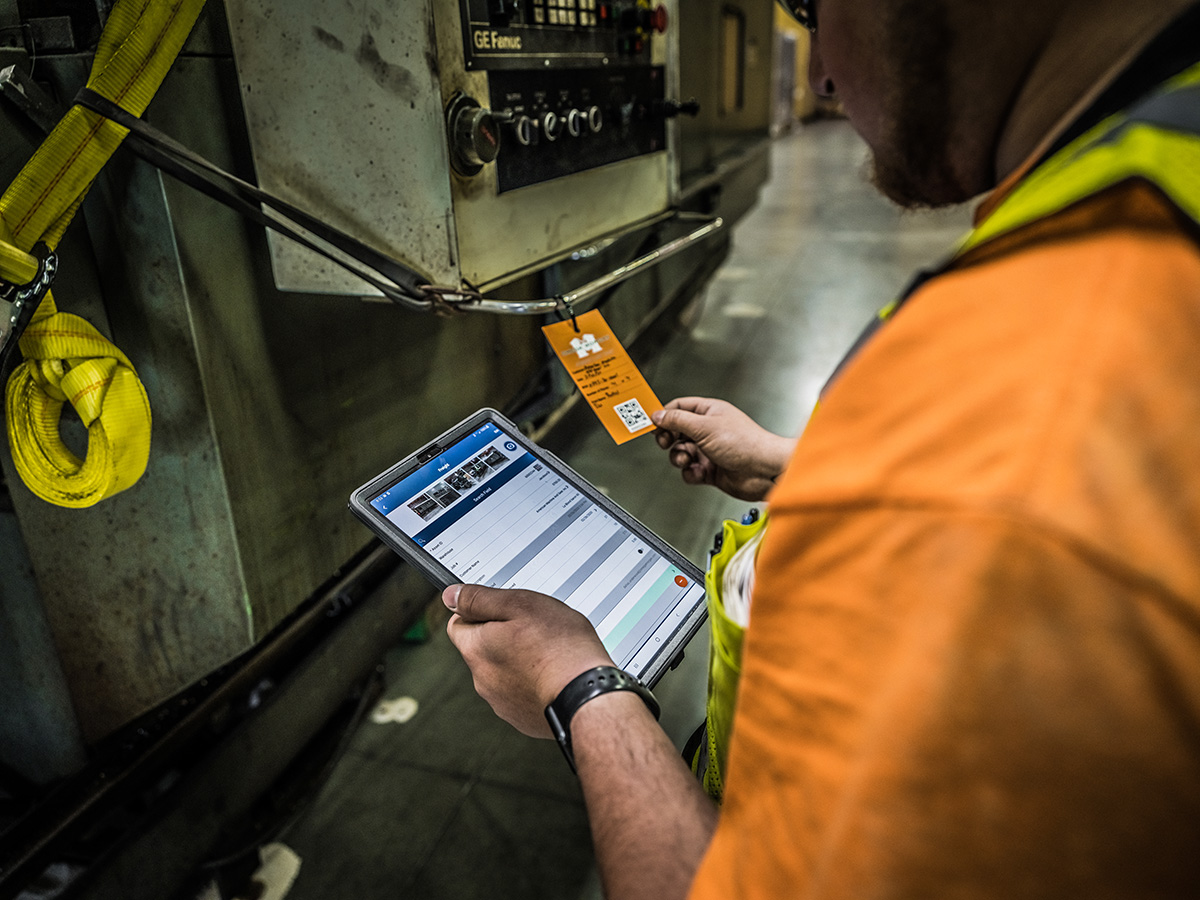 over the shoulder of an Omega Morgan staff member wearing an orange tee shirt comparing an equipment label tag to information on an iPad in a warehouse