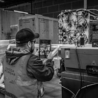deselected thumbnail button of an Omega Morgan guy photographing a piece of equipment in an Omega Morgan warehouse with an iPad