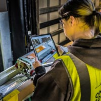 selected thumbnail button of over the shoulder of a female Omega Morgan warehouse staff member working on an ipad to go through equipment stored at the Hillsboro storage facility
