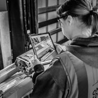 deselected thumbnail button of over the shoulder of a female Omega Morgan warehouse staff member working on an ipad to go through equipment stored at the Hillsboro storage facility