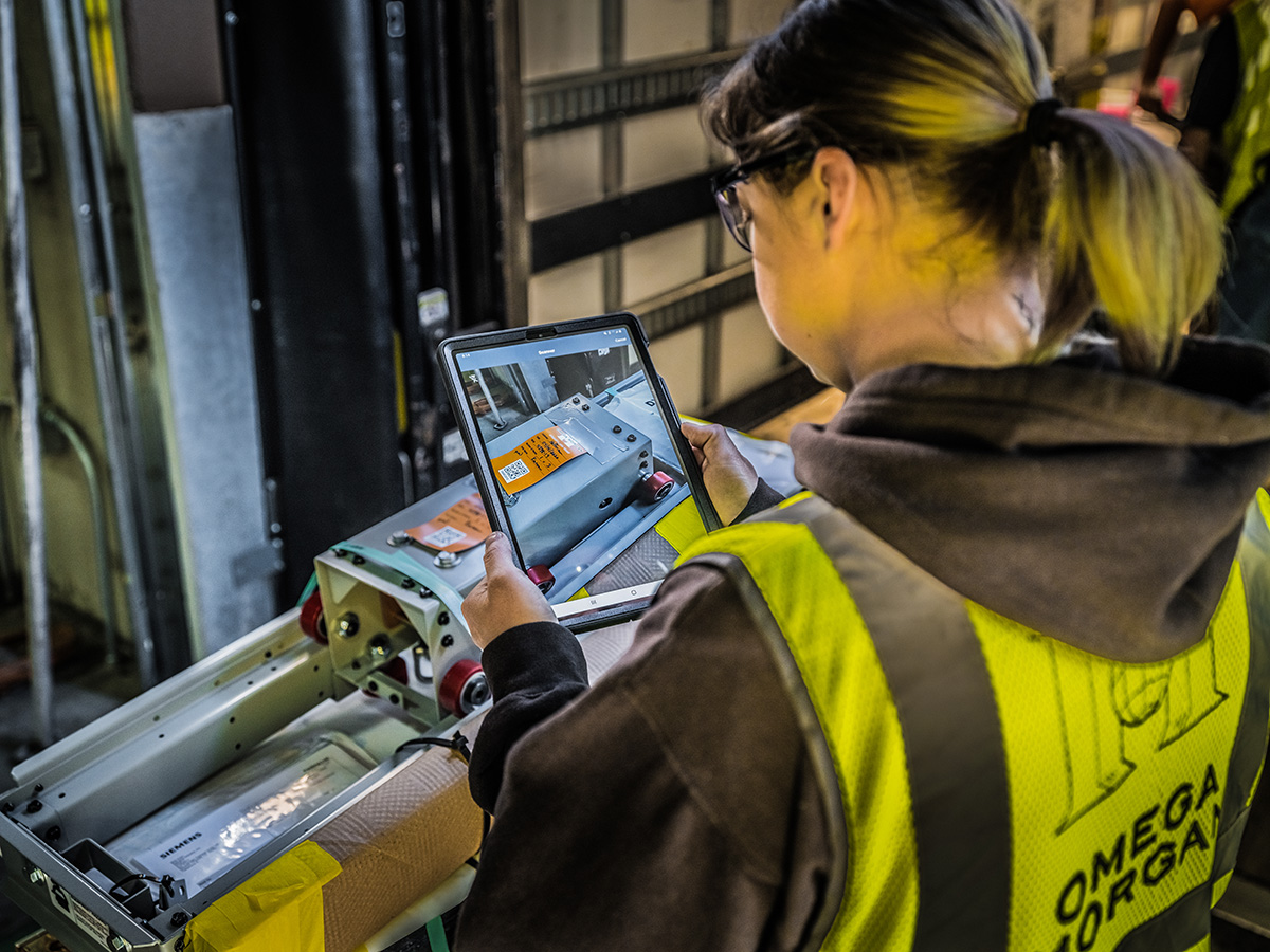 over the shoulder of a female Omega Morgan warehouse staff member working on an ipad to go through equipment stored at the Hillsboro storage facility