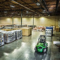 selected thumbnail button of inside an Omega Morgan warehouse and storage facility where rows of equipment are stored and a warehouse forklift is parked in front of the rows
