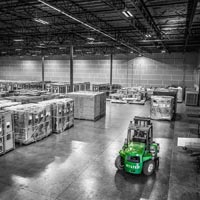 deselected thumbnail button of inside an Omega Morgan warehouse and storage facility where rows of equipment are stored and a warehouse forklift is parked in front of the rows