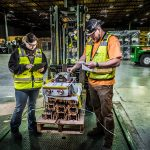 two Omega Morgan warehousing service workers inventory items on a forklift at the Hillsboro Warehouse and storage facility