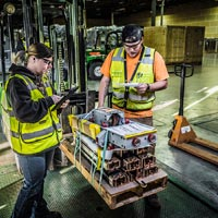 selected thumbnail button of one Omega Morgan warehouse worker with hand on a forklift load coming into the Hillsboro warehousing facility while a second Omega Morgan staff member logs items on an iPad