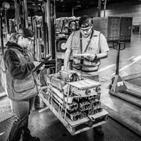 deselected thumbnail button of one Omega Morgan warehouse worker with hand on a forklift load coming into the Hillsboro warehousing facility while a second Omega Morgan staff member logs items on an iPad
