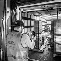 deselected thumbnail button of A man in an Omega Morgan safety vest uses an ipad to capture images of data center equipment stored at the Omega Morgan warehouse in Hillsboro, Oregon