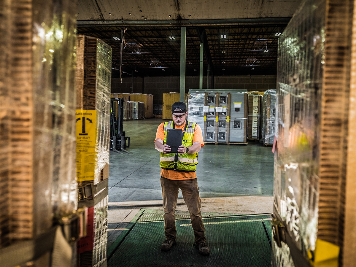 Omega Morgan warehouse and storage services team member works on an ipad in the Hillsboro warehouse facility