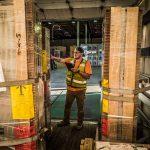 Omega Morgan warehouse employee checks boxes coming into the warehouse and storage facility