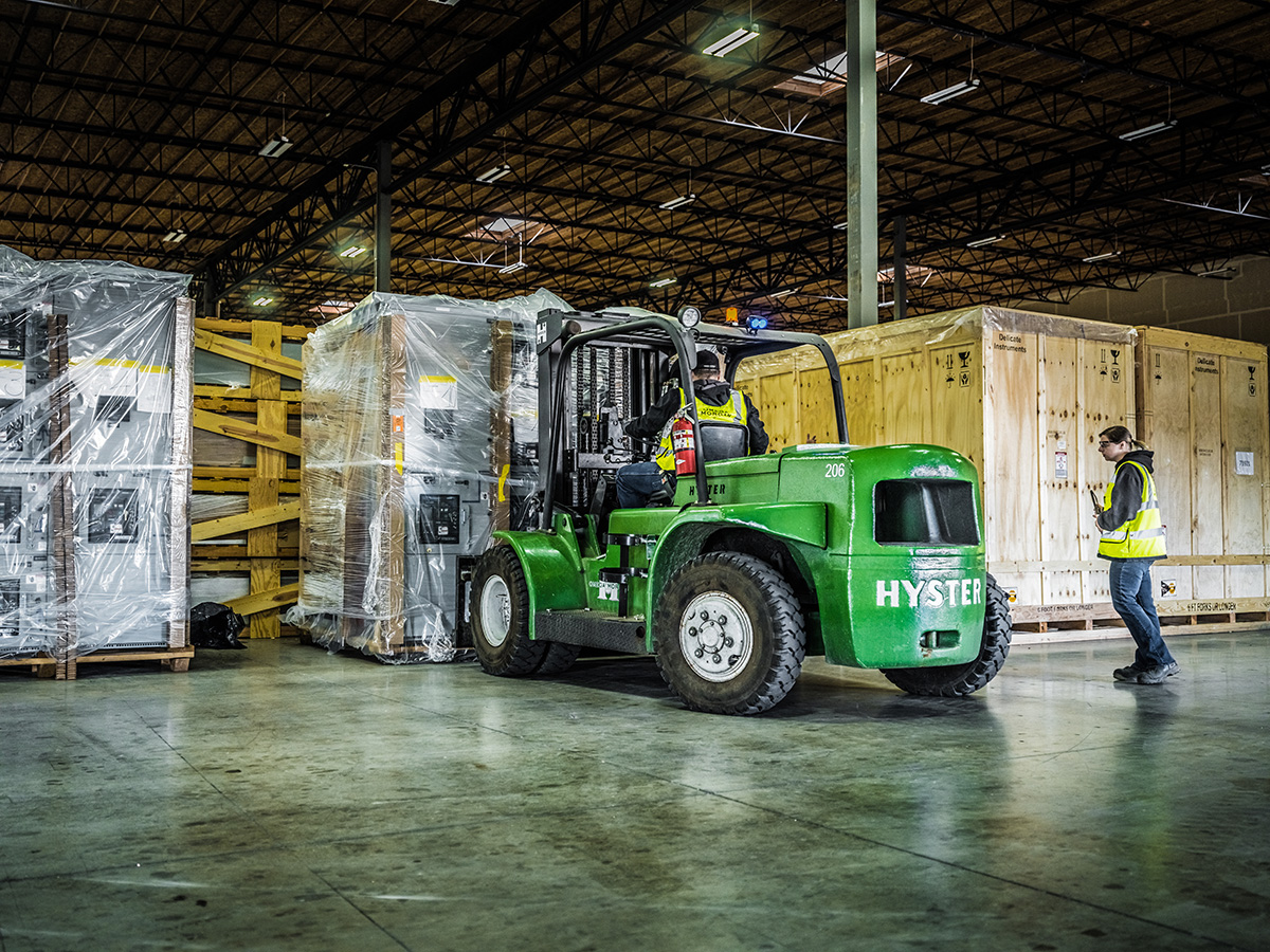 Omega Morgan hyster forklift bringing boxes wrapped in plastic into the warehouse