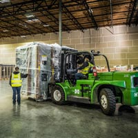 selected thumbnail button of Omega Morgan forklift operated by two Omega Morgan machinery moving crew members brings a large piece of equipment into the warehouse for storage