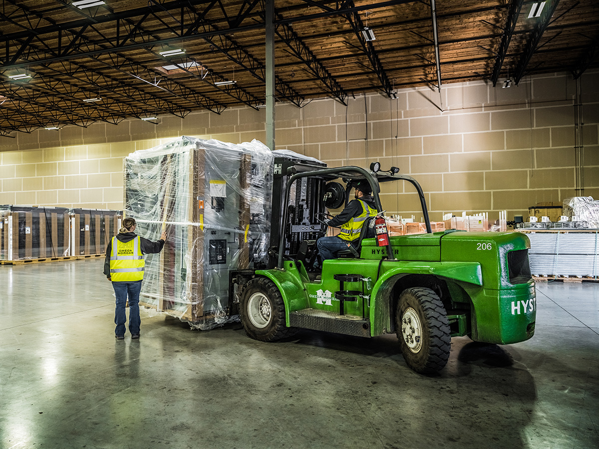 Omega Morgan forklift operated by two Omega Morgan machinery moving crew members brings a large piece of equipment into the warehouse for storage