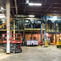 selected thumbnail button of Omega Morgan's millwright project inside a warehouse, with various lifts and equipment for moving large machinery