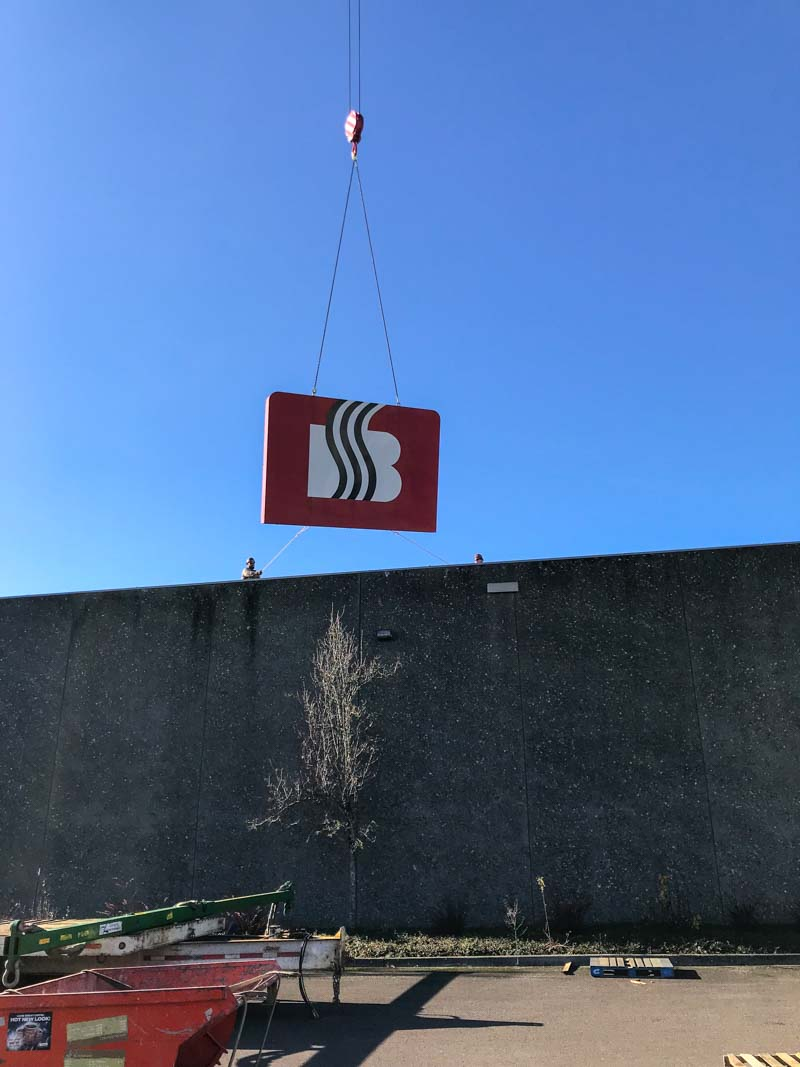 Boyd's Coffee sign being lifted via crane over a warehouse