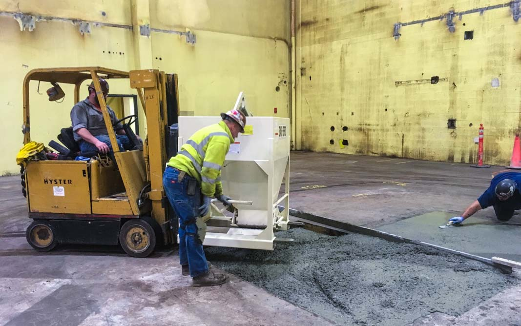 Omega Morgan team pouring concrete inside a large warehouse as part of a millwright project